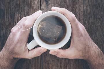 hands holding cup of steaming hot tea on old rustic wooden table
