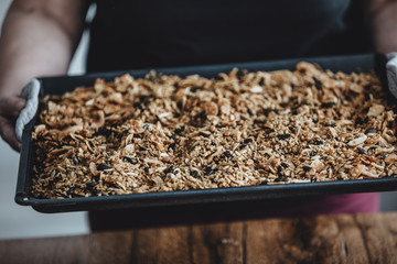 Woman holding a baking tray with freshly baked homemade granola. Healthy vegan snack easily made at home. Visible body parts of an elderly woman.