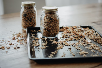 Baking tray with freshly baked homemade granola being filled in two mason jars for storage. Healthy vegan snack easily prepared at home.