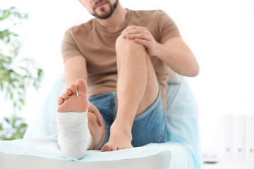 Man with broken leg in cast on couch