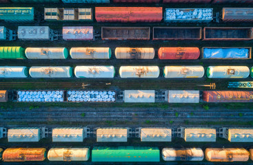 Aerial view of railway wagons. Cargo trains. Top view of colorful freight train on the railway station. Wagons with goods on railroad. Heavy industry. Industrial conceptual landscape. Transportation