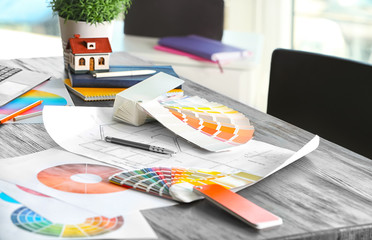 Color palette samples and house plan on table