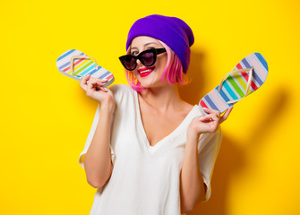 Young girl with pink hair in purple hat and sunglasses holding a flip flops shoes on yellow background