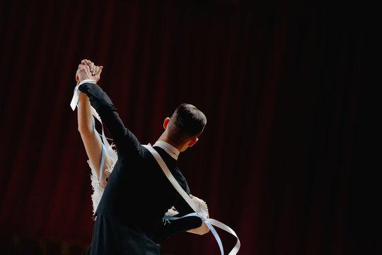 back couple ballroom dancers dancing on dark background