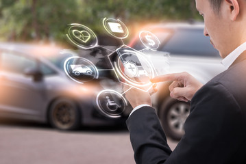 The abstract image of businessman point to the hologram on his smartphone and blurred car accident is backdrop. the concept of communication, network, insurance, financial and internet of things.