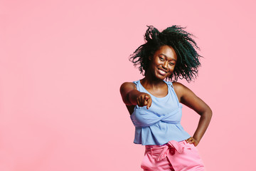 Cool young girl with blue tinted hair pointing and smiling at camera, isolated on pink studio background