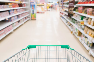 Supermarket aisle product shelves with empty green shopping cart defocused customer background