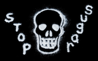 white sugar crystals forming a skull on a black background with text 'stop sugar'.