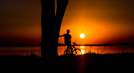 Silhouette of young man sitting on a bicycle