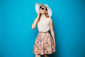 Beautiful and fashionable blonde model girl in beige blouse, pink skirt, stylish sunglasses and hat smiling and posing in studio at blue background Wall mural