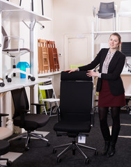 Saleswoman offering office chair in store