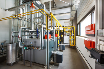 The interior of an industrial boiler house with a multitude of pipes, boilers and sensors