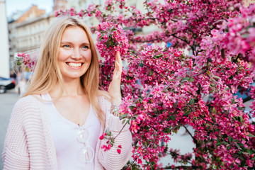 Friendly portrait positive blond student woman over spring blossom trees city street background. Tourism, travel and new impression concept.