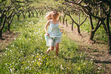 Smiling woman running among flowers