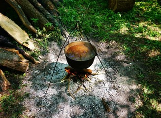 Hanging cast iron pot with water, which is heated on a fire.