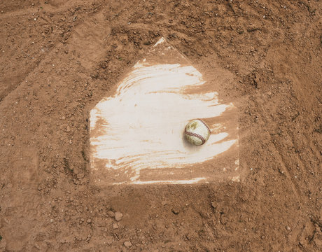 Baseball laying with homeplate on dirt field for game.