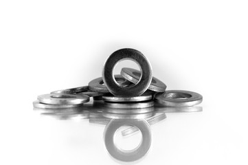 Steel round washers laid in an arbitrary shape on the reflective surface or a white background.