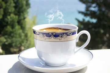 Cup of hot coffee on terrace with blurred sea and trees in the background
