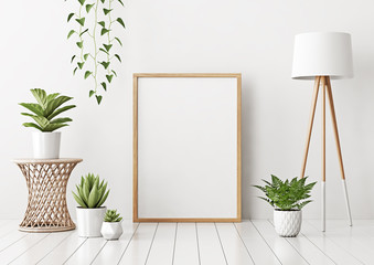 Home interior poster mock up with vertical empty wooden frame standing on floor, wicker rattan table, green plants and lamp in living room with white wall. 3D rendering.