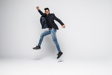 Happy Indian man jumping in the air isolated on white.