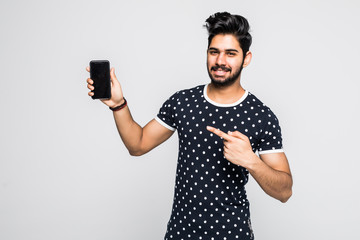 Young indian man pointing at smart phone screen against white background.