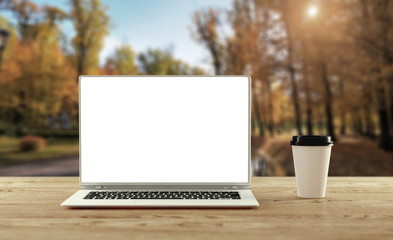 Laptop stands on wooden table outdoors. Remote office concept. 3d illustration. Mockup