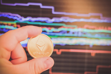 golden ethereum in the hand of a man