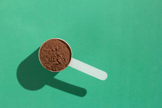 Whey Protein. Minimal concept and hard light. Scoop with chocolate flavoured powder on green background.