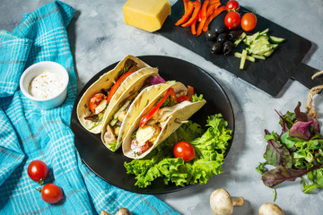 Fresh delicious mexican tacos and food ingredients on concrete rustic background.
