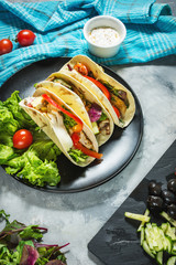 Fresh delicious mexican tacos and food ingredients on concrete rustic background