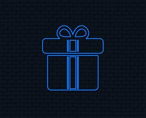 Neon light. Gift box sign icon. Present with ribbons symbol. Glowing graphic design. Brick wall. Vector