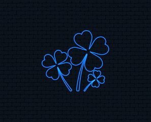 Neon light. Clovers with four leaves sign icon. Saint Patrick symbol. Glowing graphic design. Brick wall. Vector