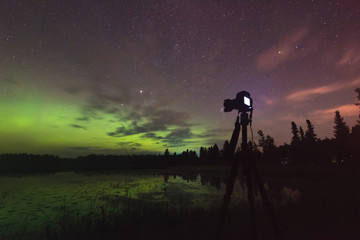 Aurora reflecting of a lake, city lights lighting up clouds - Camera in forground