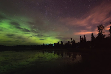 Aurora reflecting of a lake, city lights lighting up clouds