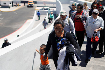 Members of a caravan of migrants from Central America enter the United States border and customs facility, where they are expected to apply for asylum, in Tijuana
