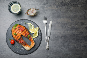 Slate plate with tasty salmon steak on grey background