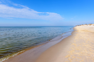 Sea waves and sandy beach in sunny day. Baltic Sea, Poland