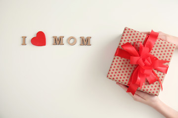 Phrase I LOVE MOM and child with gift box for Mother's Day on light background, top view
