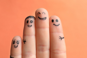Fingers with drawings of happy faces against color background. Unity concept