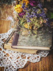 Still life with old books, dry bouquet and lace on wood