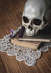 Still life with human skull and old vintage book on wood