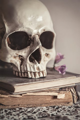 Still life with human skull and old vintage book on lace