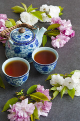 Tea concept, cups with tea and traditional teapot decorated with blooming spring tree branch