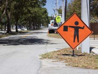Flagman sign with blurred heavy equipment in distance
