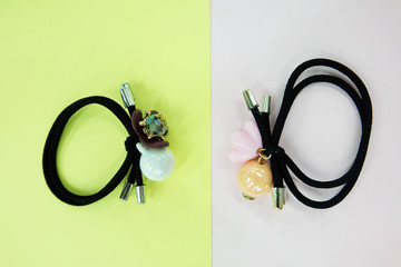 Black Rubber Band with Bead Fashion Accessories. Hair Elastic Band with Free Space. Black Hair Band with Colorful Hair Clip Isolated on Pink and Yellow Background
