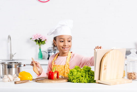 cheerful african american kid in apron and chef hat cooking on kitchen