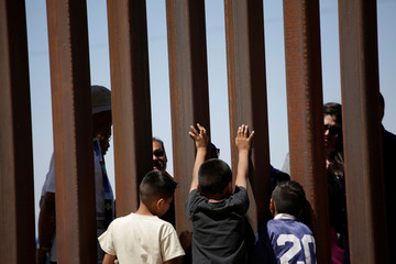 Children interact with members of the Presbyterian church in Sunland Park, U.S. at a new section of the border wall on the U.S.-Mexico border after a liturgy to commemorate the religious dimensions of migration, in this picture taken from Anapra neighborho