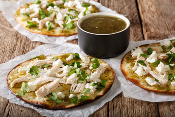 Delicious hot chalupas with chicken, cheese and green sauce close-up on the table. horizontal