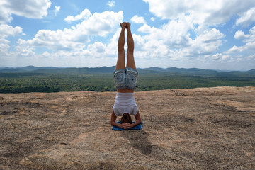 caucasian woman in yoga asana is standing on the top of the hill. Active hiking and lifestyle