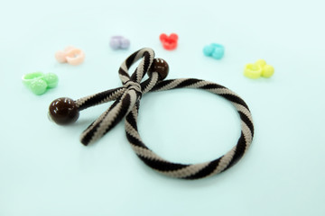 Brown Hair Rubber Band with Pearl Fashion Accessories. Top View. Rubber Band with Colorful Hair Clip Isolated on Blue Background